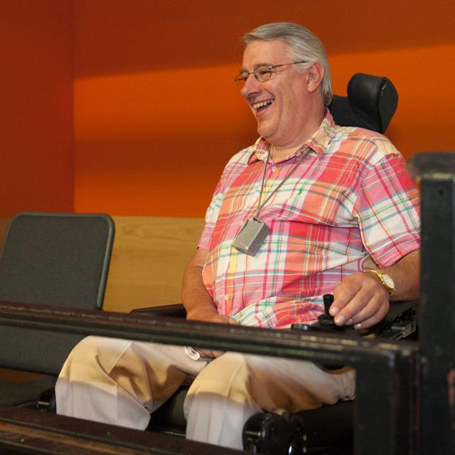 A man using a wheelchair smiles whilst sitting in the auditorium